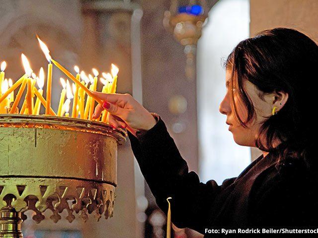 Weihnachten in Bethlehem: Frau zündet Kerzen in der Geburtskirche an, Foto: Ryan Rodrick Beiler/Shutterstock.com